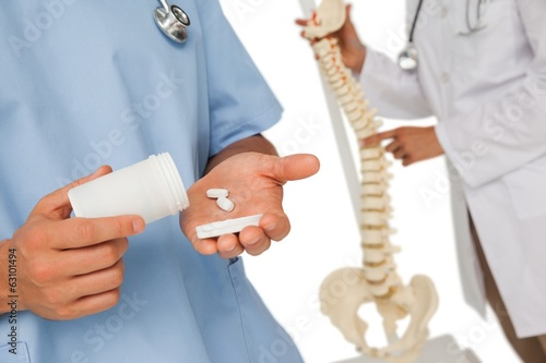 Mid section of doctors with pills and skeleton model