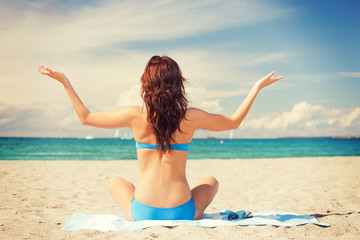 woman practicing yoga lotus pose on the beach