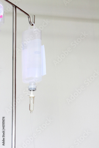 Infusion bottle with IV solution on white background