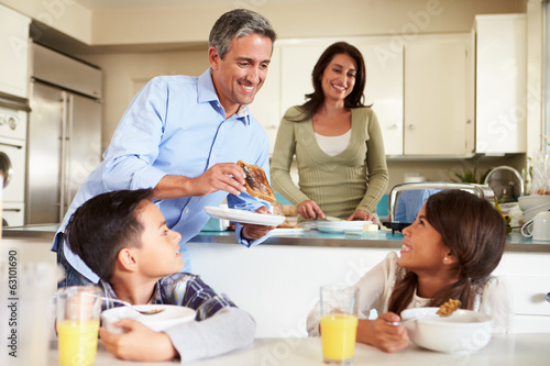 Hispanic Family Eating Breakfast At Home Together