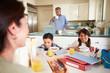 Hispanic Family Eating Breakfast At Home Before School