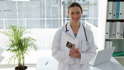 Doctor leaning on desk smiling at camera