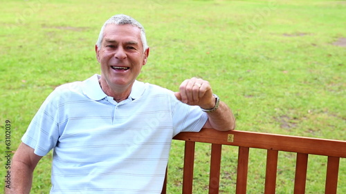 Retired man sitting on a park bench talking to the camera