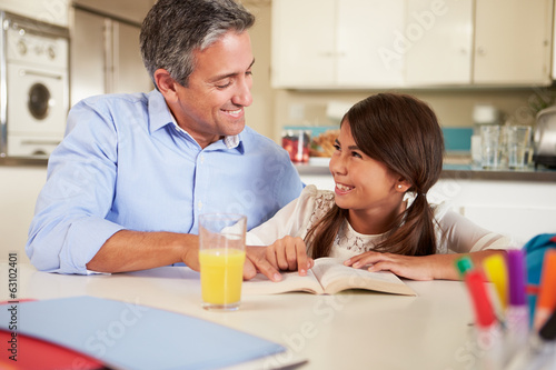 Father Helping Daughter With Reading Homework At Table