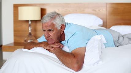 Senior man lying on bed thinking