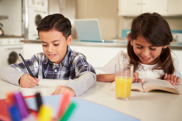 Children Doing Homework Together At Table