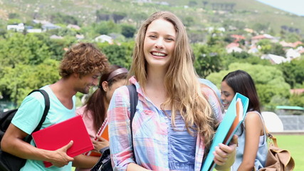 Pretty student smiling at camera with classmates behind