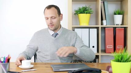 Businessman having coffee break during work in the office