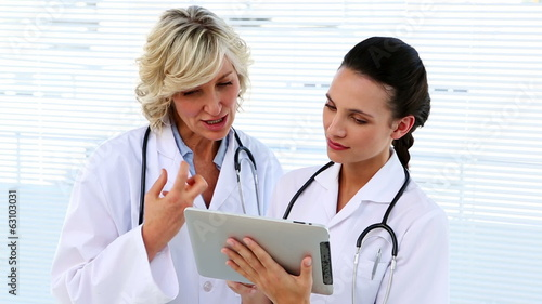 Doctor and nurse discussing something on tablet