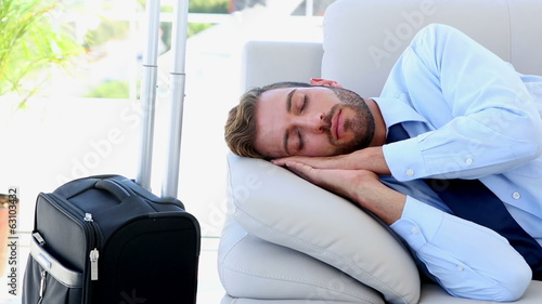 Businessman sleeping on the couch waiting to go on a trip