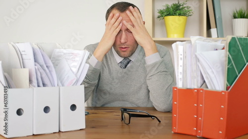 Sad, overwhelmed by too much paperwork businessman in the office