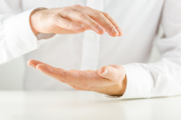 Man cupping his hands in a protective gesture