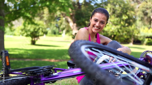 Fit girl taking off her bike helmet smiling at camera