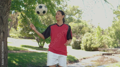Asian girl playing football in the park