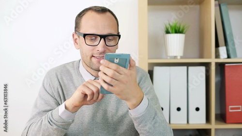 Young businessman with smartphone in the office