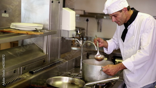 Handsome chef stirring a large pot