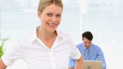 Businesswoman smiling at camera with colleague behind her