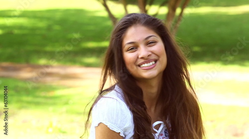 Pretty girl sitting on the grass smiling at camera