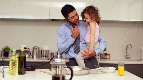 Smiling father holding his young daughter talking on the phone