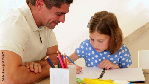 Father and daughter drawing together at the table