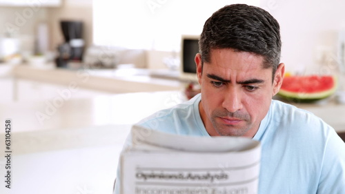 Man reading newspaper and having coffee in the morning