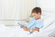 Little boy using digital tablet in hospital