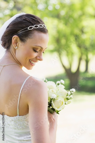 Rear view of shy bride with flowers in garden