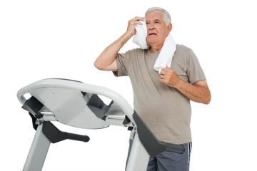 Tired senior man running on a treadmill