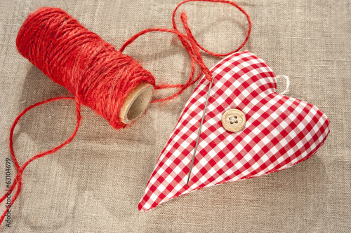 Homemade sewed red cotton love heart. Closeup.