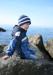 Kleiner Junge aitzt auf Wellenbrecher