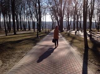 девушка идет по дорожке в парке и оглядывается назад