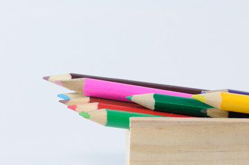 Many colored pencils in wooden box.