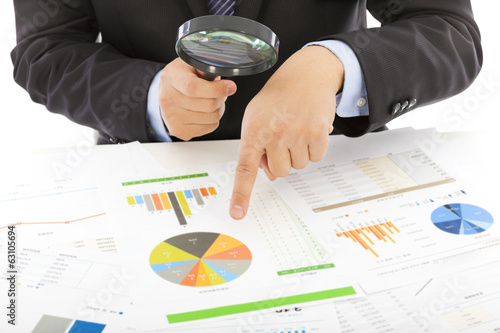 businessman hold a magnifying glass to explore