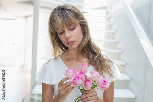 Close-up of a beautiful sad woman with flowers at home