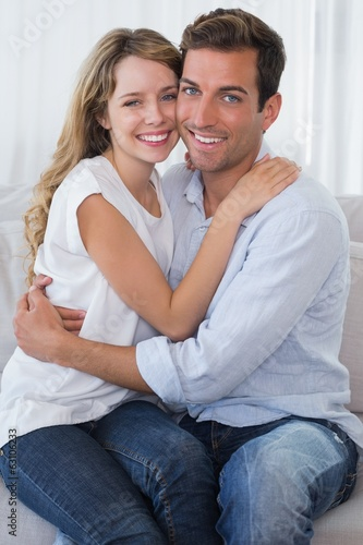 Loving young couple embracing on couch