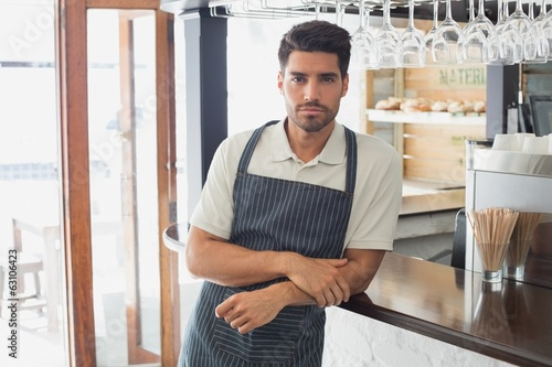 Serious confident young waiter at cafe counter