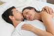 Loving young couple lying in bed at home