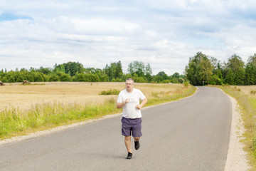 Fat man running on a rural road