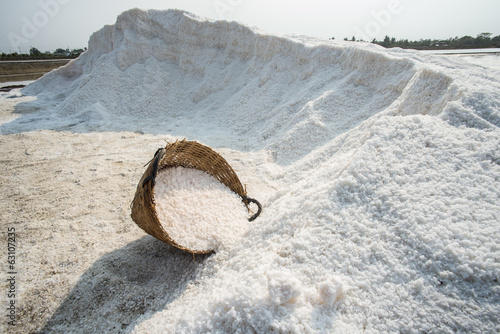 Salt in basket with background of salt pile