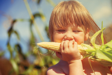 Little girl eating corn