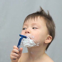 White caucasian young child shaving his beard