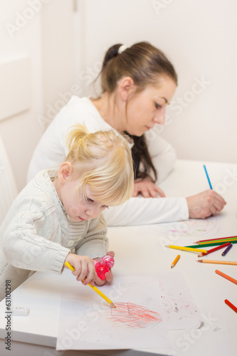 little girl drawing with colorful crayons