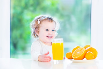 Funny curly toddler girl drinking orange juice in the morning