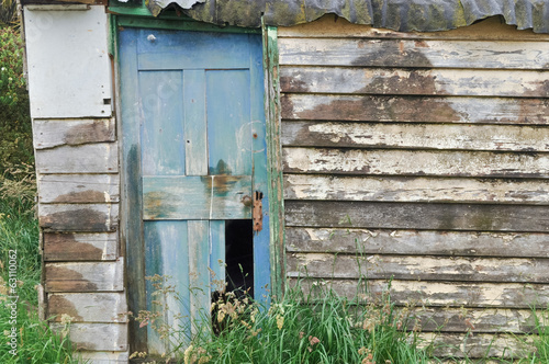 Wooden hut with weathered wooden broken door.