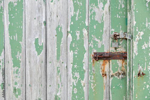 Weathered wooden door peeling green paint with rusty bolt and lo