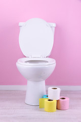 White toilet bowl and colorful rolls of toilet paper, in