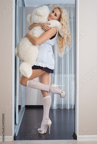 Young blond girl in erotic lingerie posing in the interior