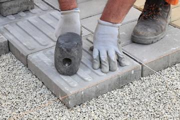 Worker installing concrete brick pavement, using hammer