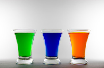 Three shot glasses with multi-colored liquid