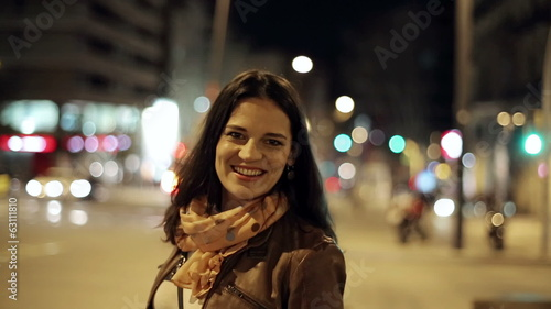 Portrait of smiling young woman in night city, steadicam shot